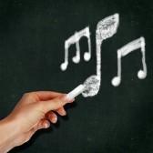 scuola-lavagna-con-il-gesso-e-la-mano-la-scrittura-di-note-musicali-su-di-esso